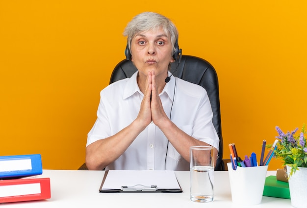 Beeindruckte kaukasische callcenter-betreiberin auf kopfhörern, die am schreibtisch mit bürowerkzeugen sitzen, die auf orangefarbener wand isoliert sind