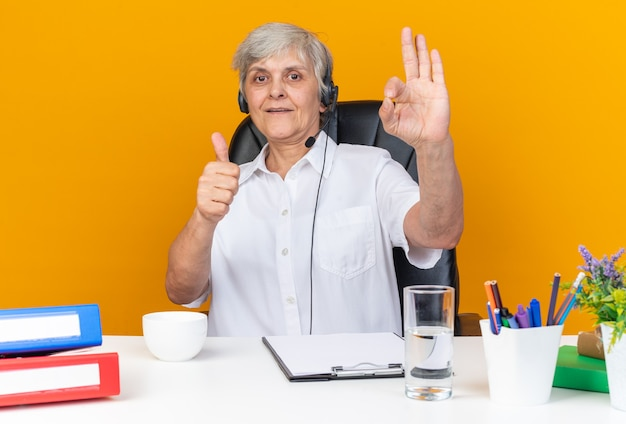 Beeindruckte kaukasische callcenter-betreiberin auf kopfhörern, die am schreibtisch mit bürowerkzeugen sitzen, die nach oben blättern und das ok-zeichen einzeln auf oranger wand gestikulieren
