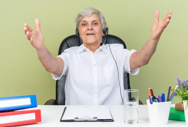 Beeindruckte kaukasische callcenter-betreiberin auf kopfhörern, die am schreibtisch mit bürowerkzeugen sitzen und die hände offen halten