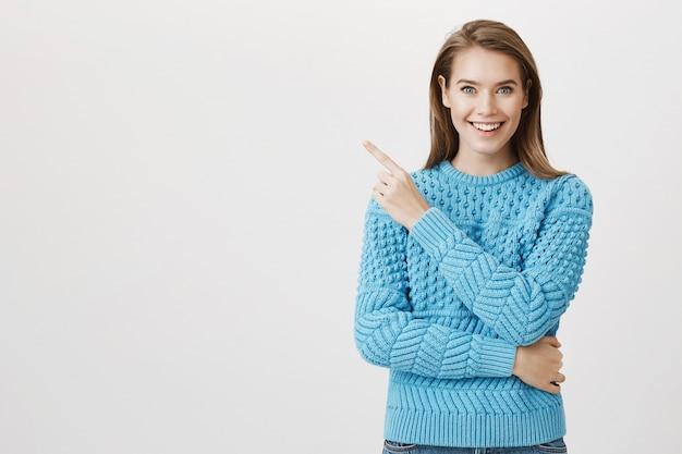 Beeindruckte lächelnde frau mit dem finger in der oberen linken ecke