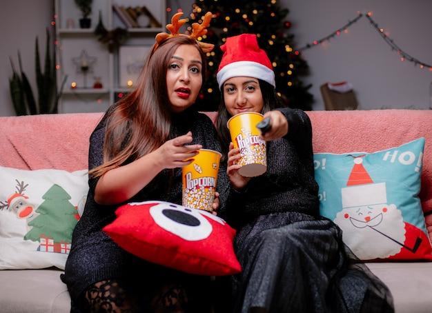 Beeindruckte mutter hält popcorn-eimer zeigt auf kamera und erfreute tochter mit weihnachtsmütze hält tv-fernbedienung sitzt auf der couch und genießt die weihnachtszeit zu hause