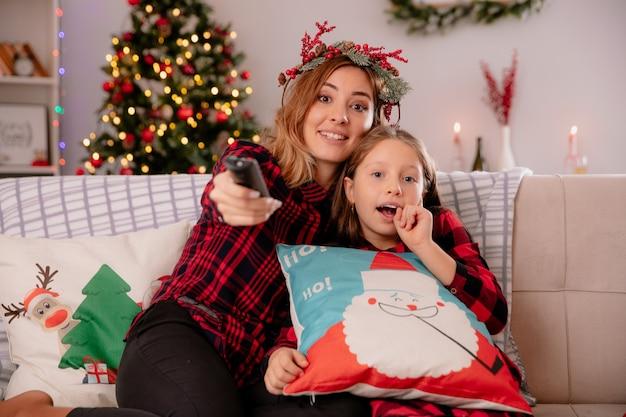 Beeindruckte mutter mit stechpalmenkranz hält tv-fernbedienung und schaut in die kamera mit tochter, die auf der couch sitzt und die weihnachtszeit zu hause genießt