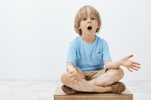 Beeindruckte neugieriges blondes kind mit vitiligo, das mit gekreuzten füßen und fallendem kiefer sitzt und handflächen spreizt