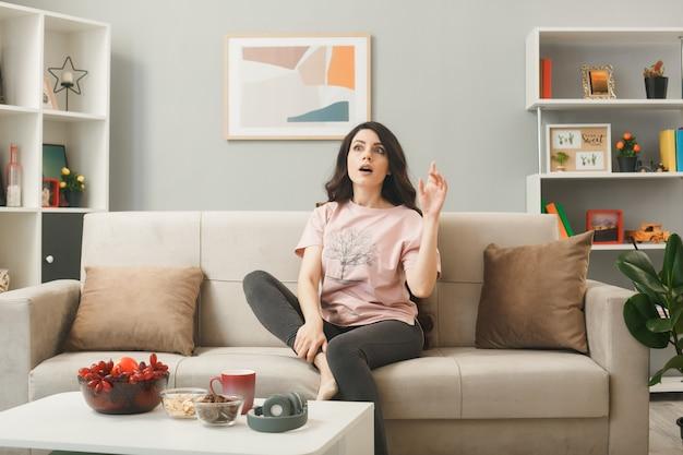 Beeindruckte punkte auf junges mädchen, das auf dem sofa hinter dem couchtisch im wohnzimmer sitzt