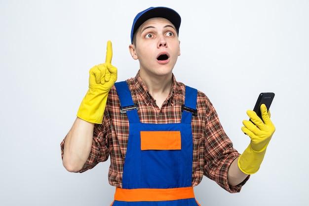 Beeindruckte punkte bei jungen reinigungskräften in uniform und mütze mit handschuhen, die telefon halten