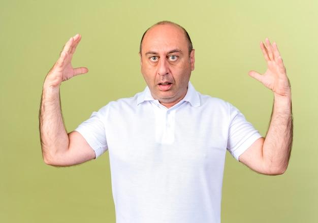 Beeindruckte reifen mann zeigt größe isoliert auf olivgrün