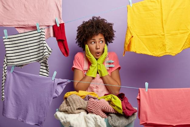 Beeindruckte schockierte junge frau mit einem afro, der mit wäsche im overall posiert