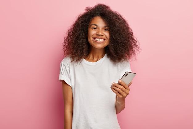 Beeindruckte schöne afro-frau mit luxuriösem lockigem haar, hält modernes handy, wartet auf anruf