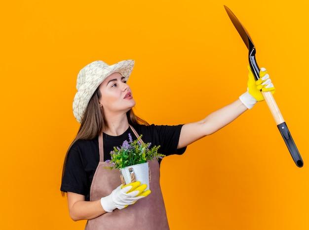 Beeindruckte schöne gärtnerin, die uniform und gartenhut mit handschuhen trägt, die blume im blumentopf halten