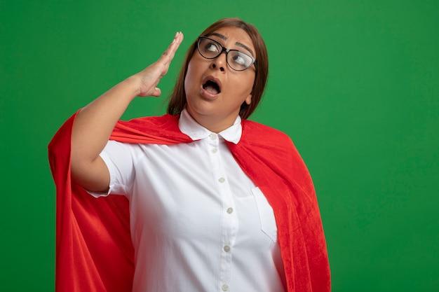 Beeindruckte superheldenfrau mittleren alters, die die seitliche tragende brille betrachtet, die hand lokalisiert auf grünem hintergrund erhöht