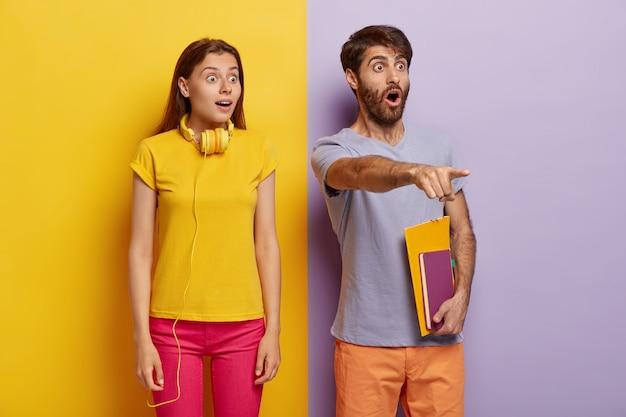Beeindruckte verängstigte schülerinnen und schüler schauen mit verwanzten augen in die ferne, bemerken etwas schreckliches, tragen einen notizblock, benutzen kopfhörer und sind in helle kleidung gekleidet. menschen, reaktionskonzept.