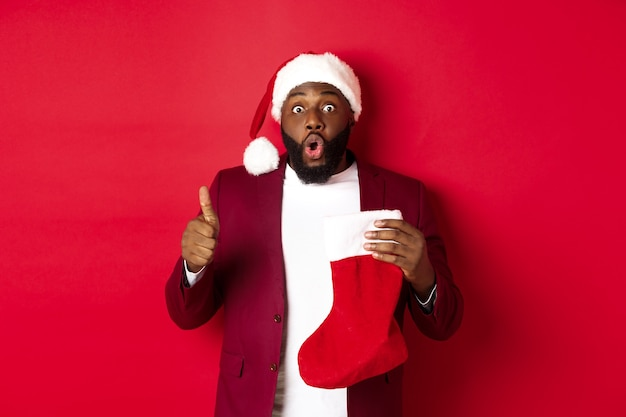 Beeindruckter afroamerikanischer mann, der weihnachtssocke mit geschenken hält, daumen nach oben zeigt, überrascht aussieht und über rotem hintergrund steht.