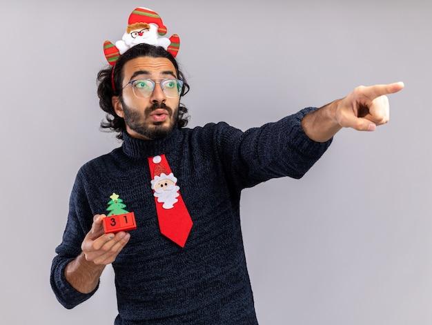 Beeindruckter blick auf den jungen gutaussehenden mann der seite, der weihnachtskrawatte mit haarbügel hält, der weihnachtsspielzeugpunkte an der seite lokalisiert auf weißem hintergrund hält