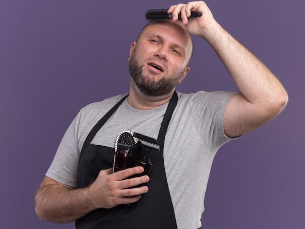 Beeindruckter blick auf den seitlichen slawischen männlichen friseur mittleren alters in uniform, der friseurwerkzeuge hält und haare kämmt, die auf lila wand isoliert sind