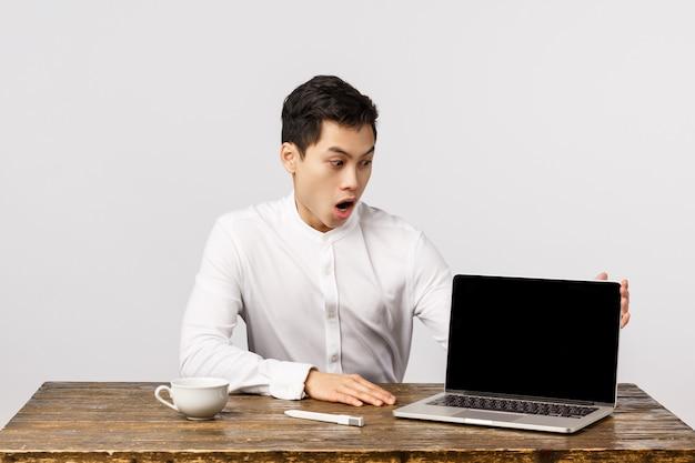 Beeindruckter, entsetzter und erstaunter junger chinesischer mann im büro, sitzende tabelle des managers, die laptopschirm schaut und etwas unglaubliches an der anzeige zeigt, sagen wow, lassen kiefer fallen und staunen