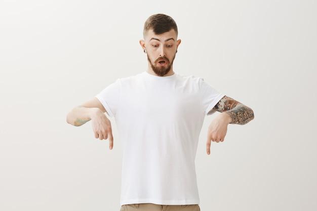 Beeindruckter erschrockener hipster-typ, der mit den fingern nach unten zeigt und die untere werbung betrachtet