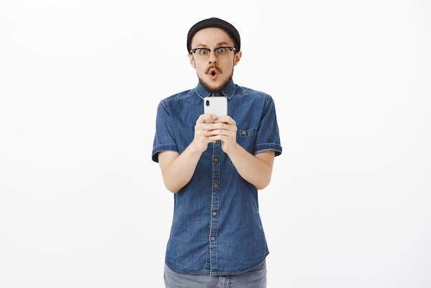 Beeindruckter erstaunter kreativer junger mann in der schwarzen mütze und in den gläsern, die lippen falten, die vor erstaunen wow halten und das smartphone halten, das aufgeregt und begeistert starrt und fantastische nachrichten erhält