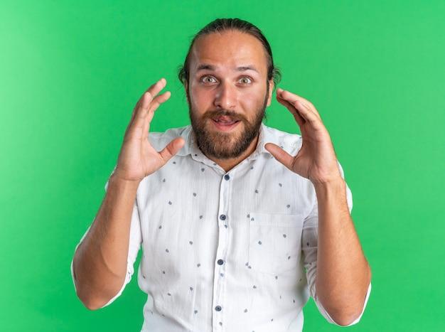 Beeindruckter erwachsener gutaussehender mann, der die hände in der luft hält und in die kamera schaut, die auf grüner wand isoliert ist