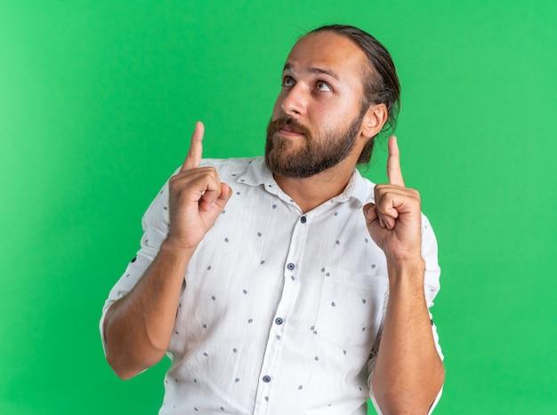 Beeindruckter erwachsener gutaussehender mann, der isoliert auf grüner wand nach oben schaut und zeigt