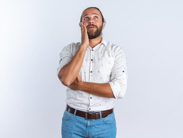Beeindruckter erwachsener gutaussehender mann mit brille, der die hand auf dem gesicht hält und isoliert auf weißer wand mit kopienraum nach oben schaut