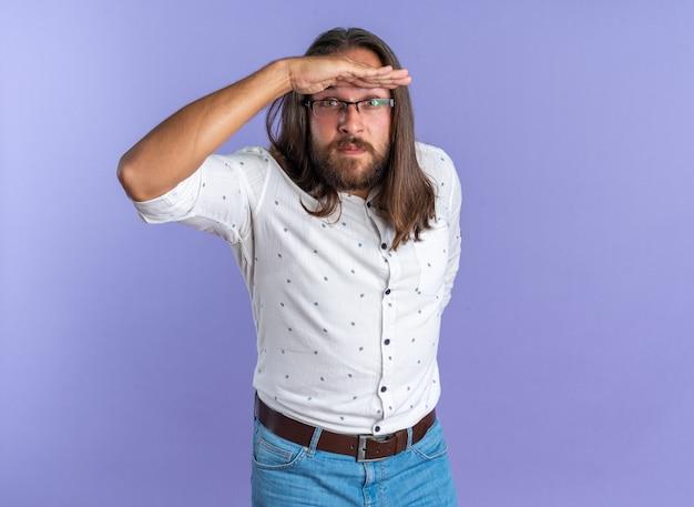 Beeindruckter erwachsener gutaussehender mann mit brille, der die hand hinter dem rücken und eine andere hand auf der stirn hält und die kamera in die ferne schaut, isoliert auf lila wand mit kopierraum