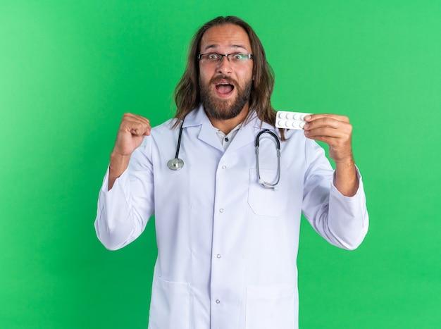 Beeindruckter erwachsener männlicher arzt, der ein medizinisches gewand und ein stethoskop mit einer brille trägt, die eine packung tabletten zeigt, die die faust der kamera einzeln auf der grünen wand betrachten