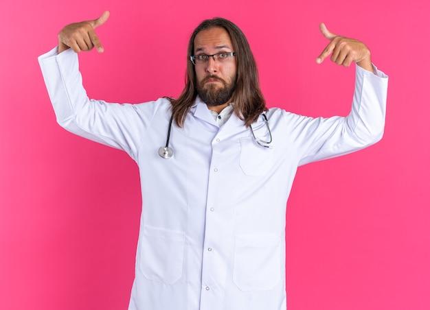 Beeindruckter erwachsener männlicher arzt, der medizinische robe und stethoskop mit brille trägt und auf die kamera blickt, die auf den raum vor ihm zeigt, isoliert auf rosa wand