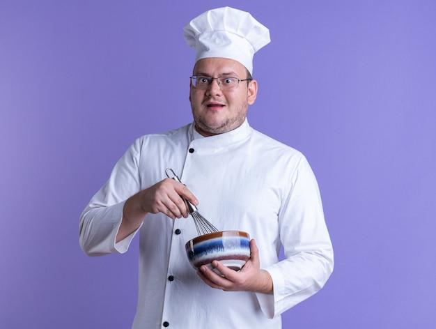 Beeindruckter erwachsener männlicher koch in kochuniform und brille mit schüssel und schneebesen, der die kamera einzeln auf violettem hintergrund betrachtet