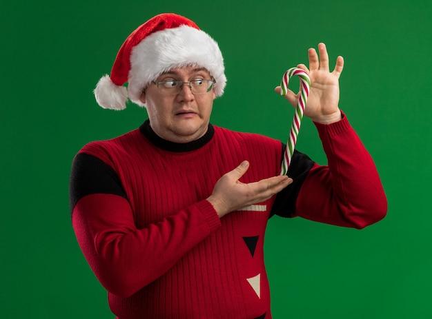 Beeindruckter erwachsener mann, der brille und weihnachtsmütze trägt, die weihnachtliches süßes rohr vertikal betrachtet, das lokal auf grünem hintergrund betrachtet