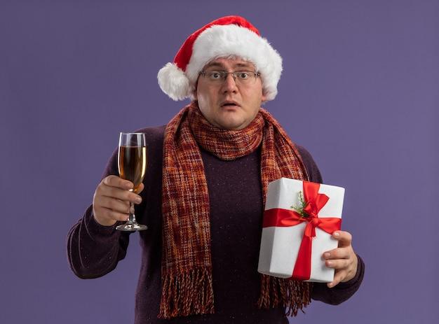 Beeindruckter erwachsener mann mit brille und weihnachtsmütze mit schal um den hals, der ein glas champagner und ein geschenkpaket isoliert auf lila wand hält