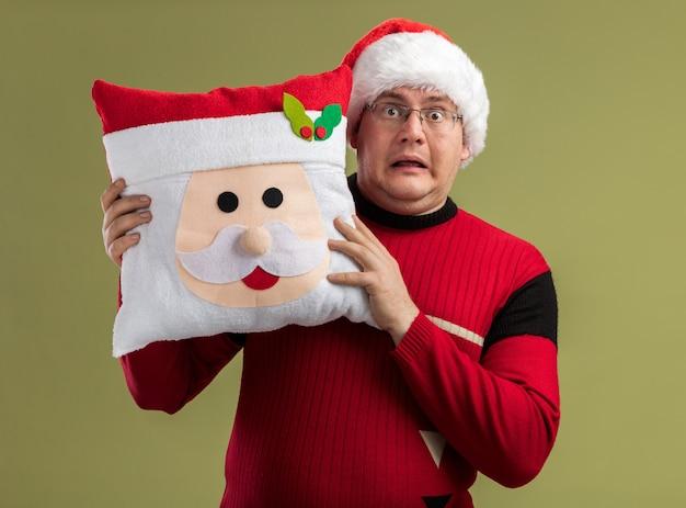 Beeindruckter erwachsener mann mit brille und weihnachtsmütze mit weihnachtsmann-kissen von hinten isoliert auf olivgrüner wand