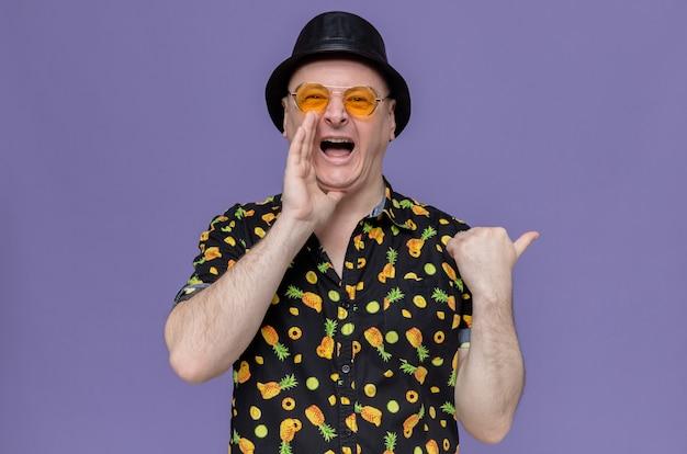 Beeindruckter erwachsener mann mit schwarzem hut, der eine sonnenbrille trägt und die hand nah an seinem mund hält und zur seite zeigt