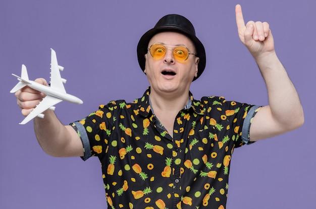 Beeindruckter erwachsener mann mit schwarzem hut mit sonnenbrille, der das flugzeugmodell hält und nach oben zeigt