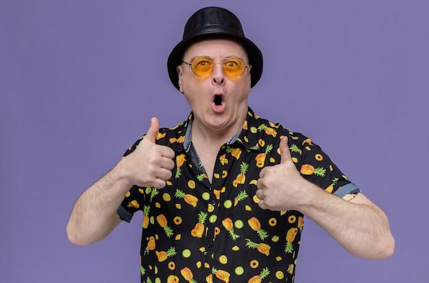 Beeindruckter erwachsener mann mit schwarzem zylinder und sonnenbrille, die nach oben greift