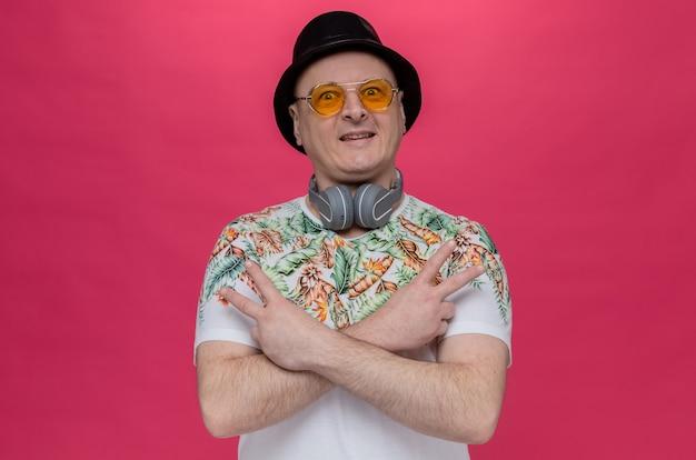 Beeindruckter erwachsener mann mit sonnenbrille und kopfhörern um den hals, der einen schwarzen zylinder trägt und das siegeszeichen gestikuliert