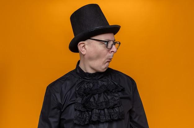 Beeindruckter erwachsener mann mit zylinder und brille in schwarzem gothic-hemd, der auf die seite schaut