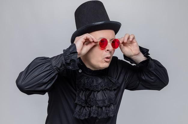Beeindruckter erwachsener mann mit zylinder und sonnenbrille in schwarzem gothic-hemd, der auf die seite schaut