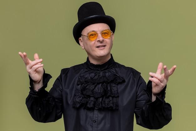 Beeindruckter erwachsener mann mit zylinder und sonnenbrille in schwarzem gothic-hemd, der die hände offen hält und schaut