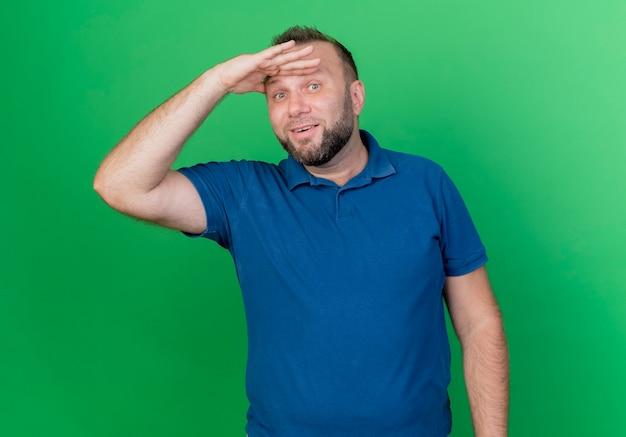 Beeindruckter erwachsener slawischer mann, der hand auf stirn legt und entfernung betrachtet