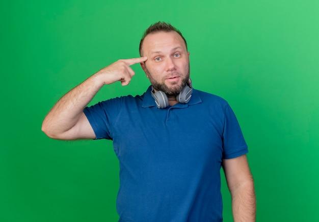 Beeindruckter erwachsener slawischer mann, der kopfhörer am hals trägt und finger auf kopf zeigt