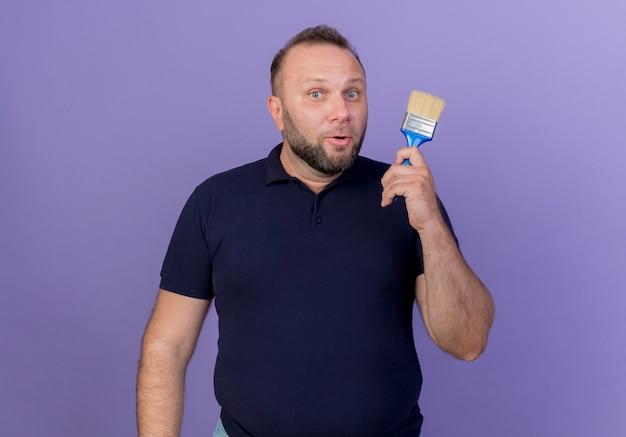 Beeindruckter erwachsener slawischer mann, der pinsel lokalisiert hält