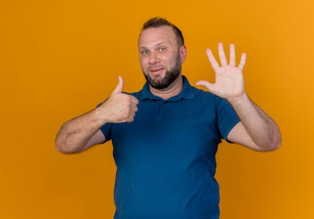Beeindruckter erwachsener slawischer mann, der sechs mit den händen zeigt