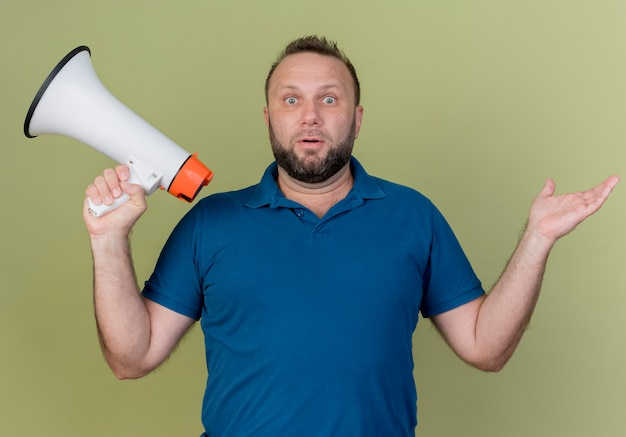 Beeindruckter erwachsener slawischer mann, der sprecher hält und leere hand zeigt