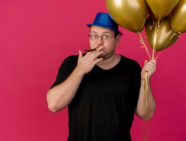 Beeindruckter erwachsener slawischer mann in optischer brille mit blauem partyhut hält heliumballons, die partypfeife blasen