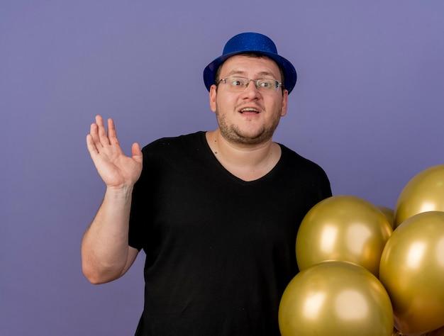 Beeindruckter erwachsener slawischer mann in optischer brille mit blauem partyhut steht mit erhobener hand neben heliumballons, die auf die seite schauen
