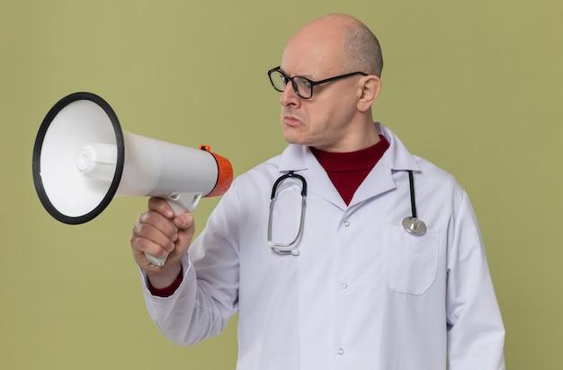 Beeindruckter erwachsener slawischer mann mit optischer brille in arztuniform mit stethoskop, das den lautsprecher hält und anschaut
