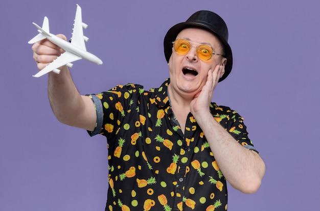 Beeindruckter erwachsener slawischer mann mit schwarzem hut mit sonnenbrille, der die hand auf sein gesicht legt und das flugzeugmodell hält