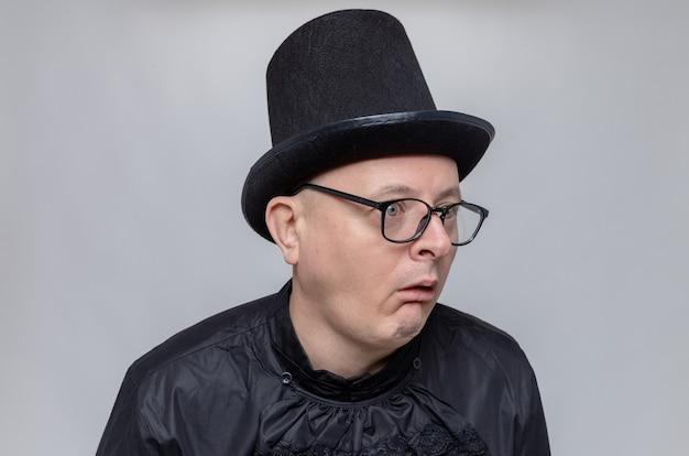 Beeindruckter erwachsener slawischer mann mit zylinder und optischer brille in schwarzem gothic-hemd mit blick auf die seite
