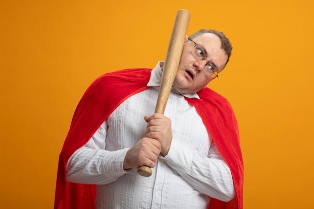 Beeindruckter erwachsener slawischer superheldenmann im roten umhang, der brille trägt, die seite betrachtet, die sich im gesicht mit baseballschläger schlägt, der auf orange wand lokalisiert wird