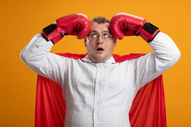 Beeindruckter erwachsener slawischer superheldenmann im roten umhang, der brille und kastenhandschuhe trägt, die kopf mit den händen berühren, die lokal auf orange wand schauen
